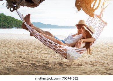 Asian couple lying on hammock on beach thailand