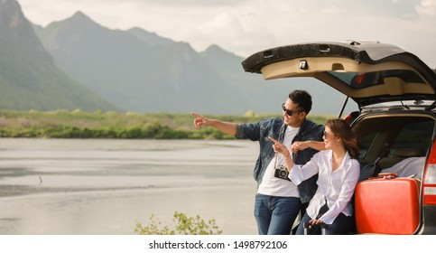 Asian couple Man with vintage camerra and woman sitting on back of car  travel to mountain and lake in holiday with car road trip