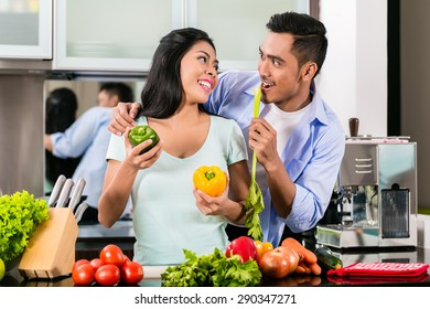 Asian couple, man and woman, cooking food together in kitchen preparing dinner