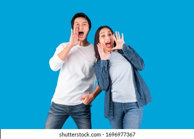 Asian couple man and woman shout and announce with loud over blue background with copy space