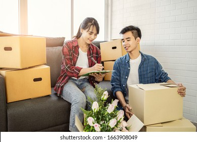 asian couple moving house packing belongings, objects and item away in a brown cardboard box, in the living room helping each other packaging and stacking boxes, smiling joyfully and working together