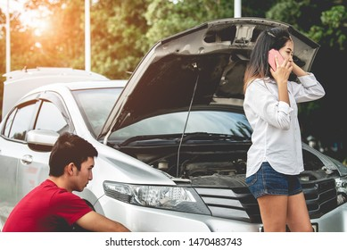 Asian couple on the road having problem with car,broken down car on the road.