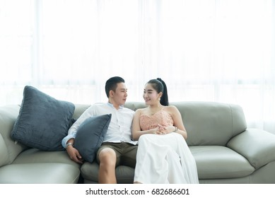Asian couple on sofa looking eyes together in the livingroom
