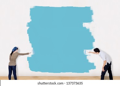 Asian couple painting the wall in blue