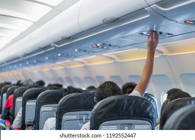 Asian couple people cabin crew, hand up to adjust console panel; the air condition, light / lamp above the low cost airline seat.