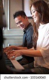 Asian Couple playing the grand piano