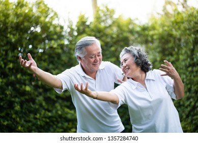 Asian Couple practicing Tai Chi in the park together.