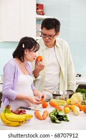 Asian couple ( pregnant wife ) busy preparing food in kitchen