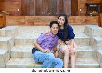 Asian couple in purple dressing sitting on a step in front of a wooden house