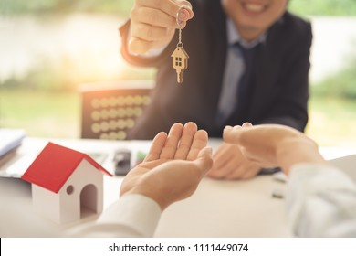 Asian couple receiving a key form real estate agent after successful housing purchase in real estate agency office. Concept of housing purchase and insurance.