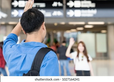 Asian couple say Hi or goodbye for abroad at airport. Back asian man waving hand goodbye girlfriend. Travel ,airport terminal concept.