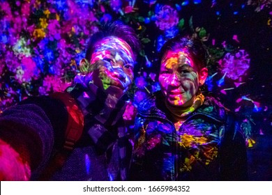 An Asian couple selfies with projector and reflecting light effect art at teamLab Borderless Tokyo Odaiba, Tokyo/Japan February 8,2020