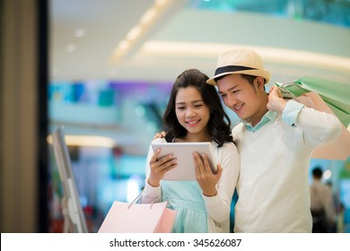 Asian couple with shopping bags watching something on digital tablet