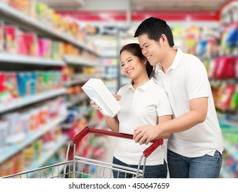 asian couple with shopping cart in supermarket