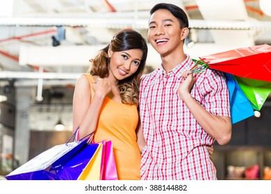Asian couple shopping in fashion store or shop with lots of bags