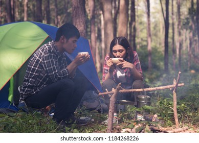 Asian couple sitting and drinking coffee in front of the tent in the camp.