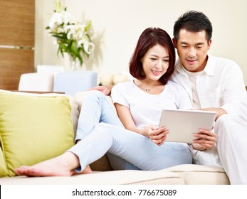 asian couple sitting on family couch in living room using digital tablet together.