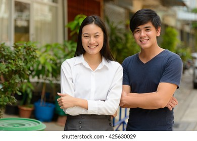 Asian couple smiling outdoors
