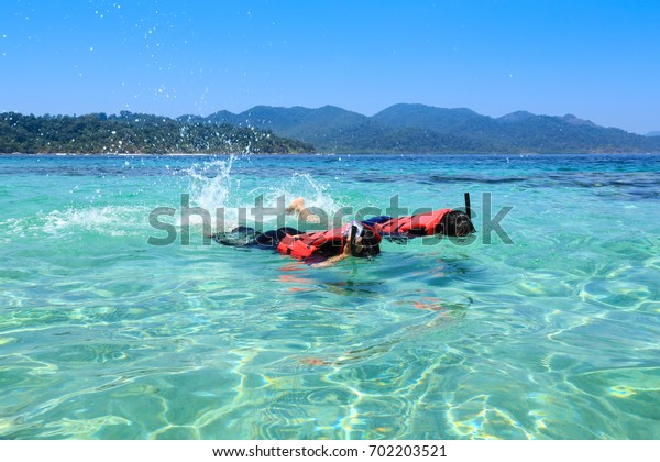 asian couple snorkel in the tropical sea