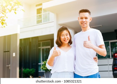 Asian couple standing in front of their new house and giving thumbs up. Newlyweds family just moved in new home and car carrying boxes