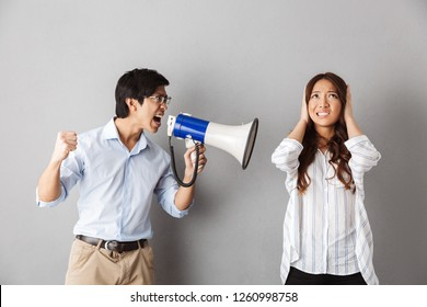 Asian couple standing over gray background, man yelling in a loudspeaker