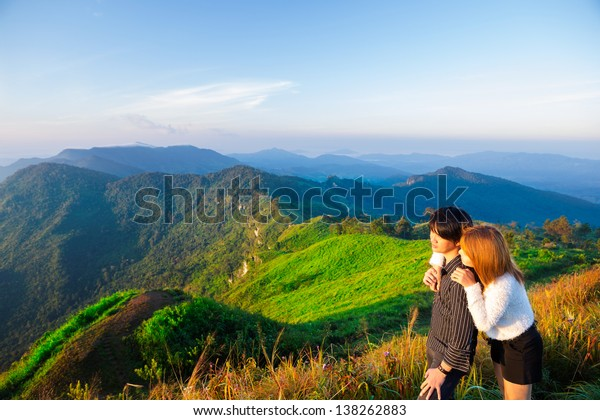 Asian couple standing over Mountains
