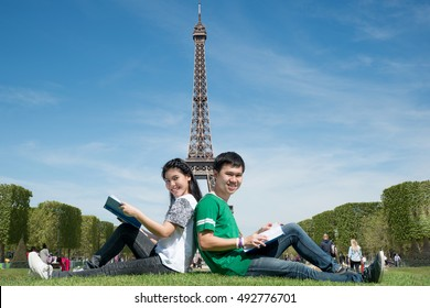 Asian couple student reading book together at outdoors park near Eiffel Tower in Paris, France. Abroad study in Paris, France.