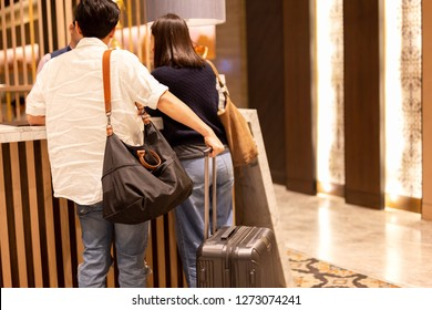 Asian couple with suitcase checking in at hotel reception.