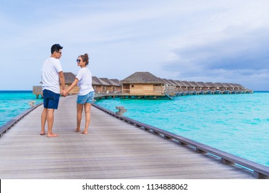 Asian couple sweetheart honeymoon traveling sea background, vacation holiday concepts with tropical Maldives island background.