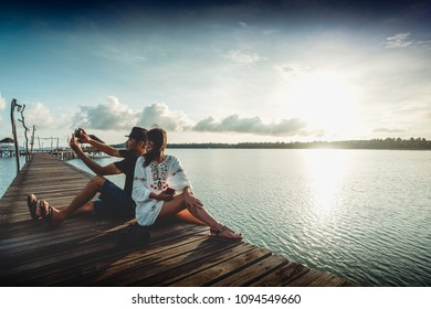 Asian couple taking a selfie by the coast on a sunny, Koh mak Trat Thailand