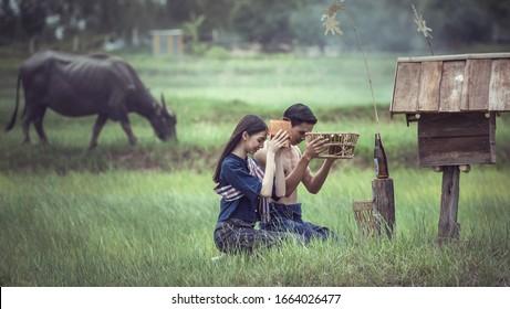 Asiatisches Paar auf thailändischem Land, Der traditionelle Glaube an Isan in Thailand, Anbetung von Phi-Ta-Hak. Phi-Ta-Hak ist der Geist der Reisfelder. Das bewahrt Pflanzen und Gärten und kümmert sich um sie.