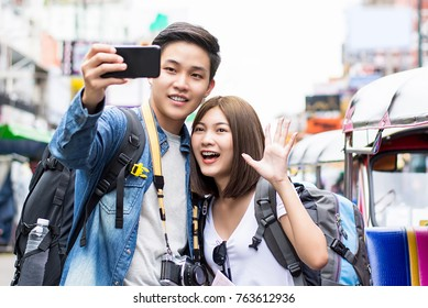 Asian couple tourist backpackers taking selfie with smartphone while traveling on holidays in Khao San road Bangkok Thailand