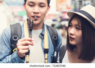 Asian couple tourist backpackers traveling on holidays, holding and looking at fried scorpion one of street food at Khao San road in Bangkok, Thailand