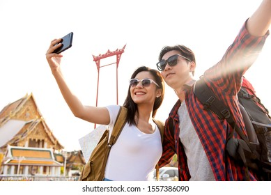 Asian couple tourists taking selfie while traveling in Bangkok Thailand with Giant Swing and Buddhist temple in background