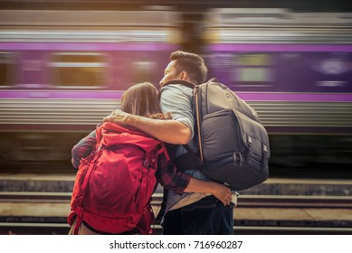 Asian couple tourists in the train station of Thailand with train movement is background.