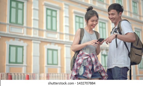 Asian couple travel Happy and Smaile using smartphone in Bangkok Thailand