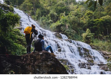 Asian couple travel nature. Travel relax. Stand landscapes Natural Touch Stand to see beautiful waterfalls mae ya at Chiangmai in Thailand
