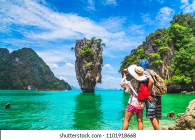 Asian couple traveler with packpack relaxing on amazing nature sea beach joy view James Bond island, Phuket, travel Thailand, Beautiful destination landscape Asia, Summer holiday outdoor vacation trip