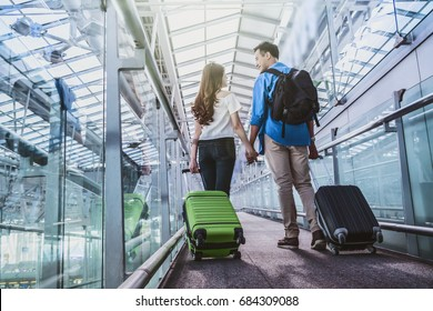 Asian couple traveler with suitcases at the airport. Lover travel and transportation with technology concept.