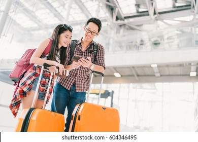Asian couple travelers using smartphone checking flight or online check-in at airport, with passport and luggage. Air travel or mobile phone technology concept.