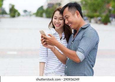 Asian couple using cell smart phone message smile standing on city street