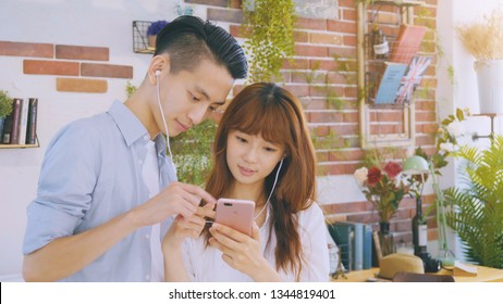 Asian couple using mobile phone in house