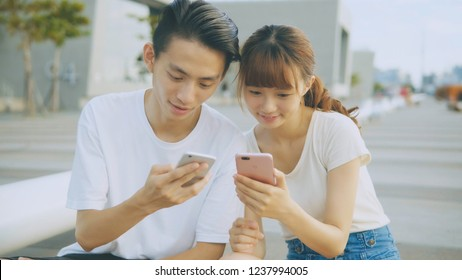 Asian couple using smart phone in park
