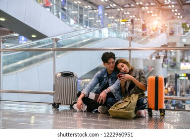 Asian couple wait boarding at the international airport to travel on weekends , tourism and holiday concept.