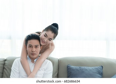 Asian couple watch television in the livingroom,woman hug man from back