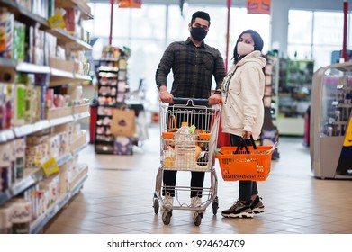 Asian couple wear in protective face mask shopping together in supermarket during pandemic.