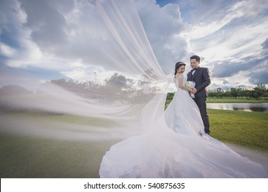 asian couple wedding outdoor style under a cloudy sky on a green grass field with bride's suit's part spreading in the air