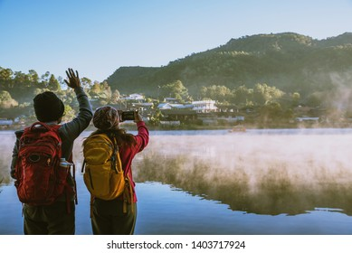 An Asian couple who is standing and watching the fog rising on the lake in the morning. Travel Ban Rak Thai village, Mae Hong Son in Thailand. Take a picture of the lake