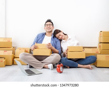 Asian couple working at home with business shopping online happy with good order box shipping background