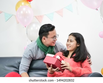 Asian couple young Man and woman give Christmas present gift box in Party living room